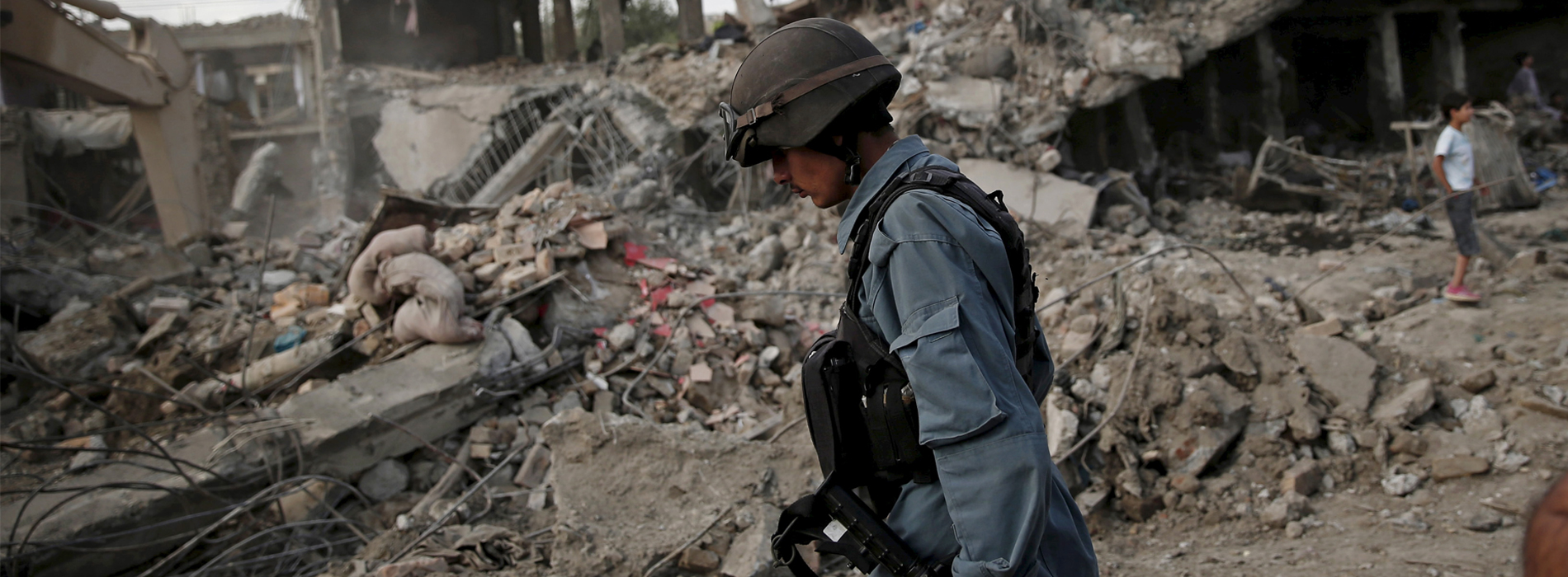 Afghan policeman walks at the site a truck bomb blast in Kabul, August 7, 2015. A truck bomb exploded near an army compound in Kabul on Friday, killing at least 15 people and wounding another 248, police and government officials said, in the first major attack in the Afghan capital since the Taliban announced a new leader. REUTERS/Ahmad Masood