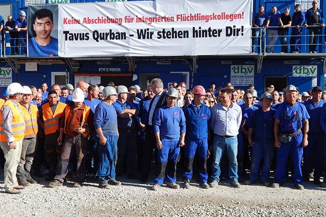 """Bild: Viele Kollegen im Blaumann stehen vor Werkshalle, in er Mitte Tavus Qurban, darüber ein Banner mit dem Spruch """"Keine Abschiebung für integrierten Flüchtlingskollegen! Tavus Qurban - Wir stehen hinter Dir!"""""""