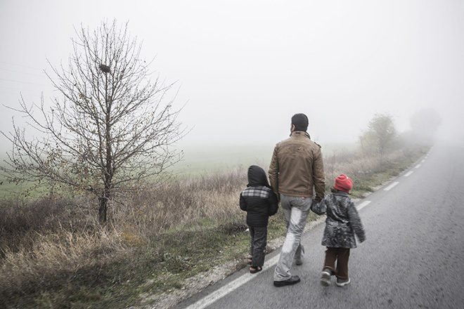 Bild von einem Vater mit zwei kleinen Kindern an der Hand auf einer einsamen Landstraße, die ins Nirgendwo zu führen scheint.