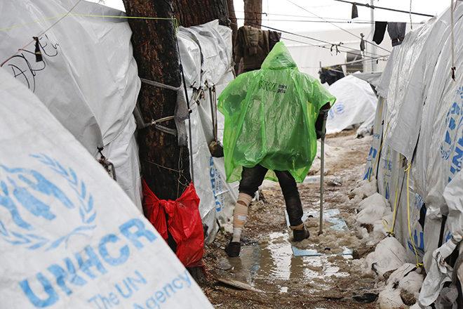 Bild: EU-Hotspot Moria auf Lesbos: Ein Flüchtling bahnt sich auf Krücken den Weg durch Schlamm und Schneematsch zwischen den Zelten, Januar 2017