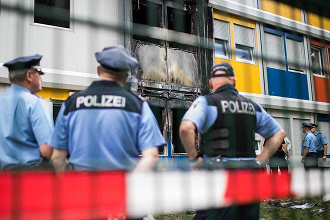 Bild: Anschlag auf eine Flüchtlingsunterkunft in Berlin-Buch: Polizisten begutachten die Brandstelle, Aug. 2016