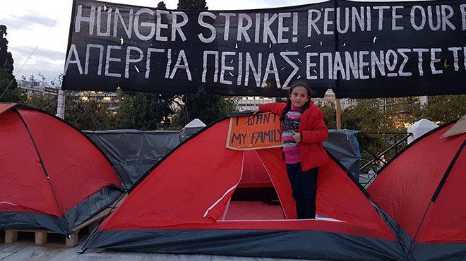 """Bild: Mädchen steht vor einem Zelt mit einem Plakat """"I want my family"""", im Hintergrund ein banner auf Englisch und Greichisch, dass den Familiennachzug innerhalb der EU fordert."""
