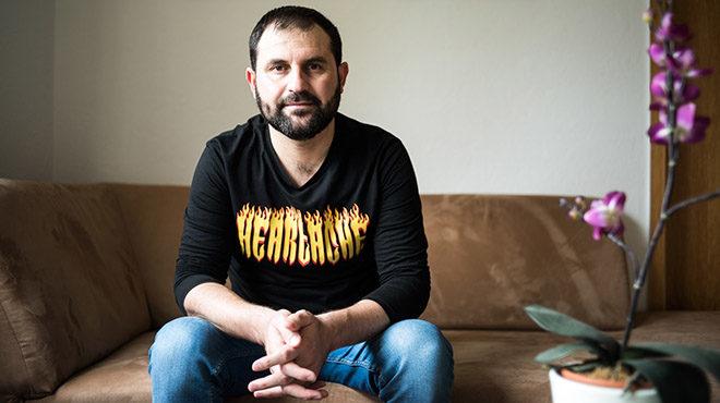 Bild: Anas in Jeans und T-Shirt auf dem Sofa, guckt offen und freundlich in die Kamera