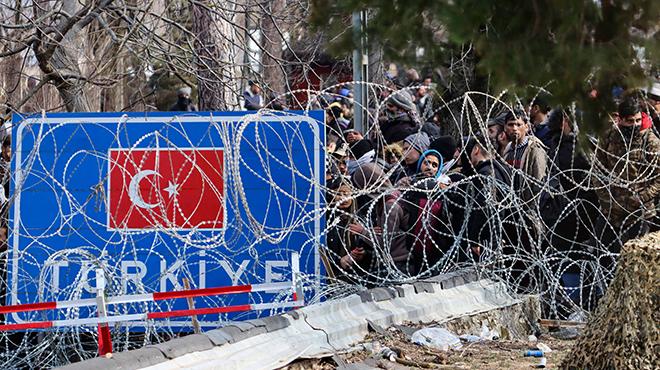 Geflüchtete vor Stacheldraht an der türkisch-griechischen Grenze