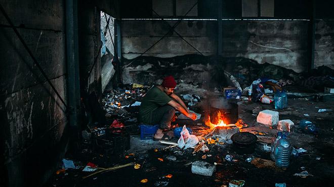 Junger Flüchtling in Bosnien am Feuer in einer Lagerhalle