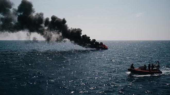 Rettungsboot im Mittelmeer vor brennendem Schlauchboot